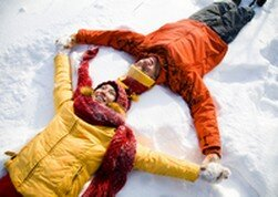 two people lying on the snow